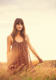 Beautiful woman in golden field at sunset Royalty Free Stock Photo