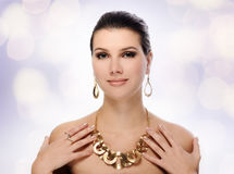 Beautiful woman in golden jewelry Stock Images