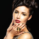 Beautiful woman with golden nails and fashion makeup Stock Image
