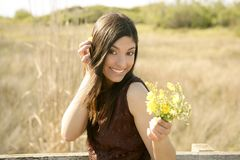 Beautiful woman in golden outdoor, yellow flower Stock Photos