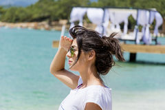 Beautiful woman with golden  sunglasses  on a sea background Royalty Free Stock Image