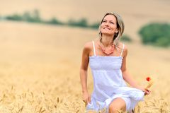 Beautiful woman in golden wheat field Stock Image