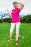 Beautiful woman on golf course looking behind flying ball Royalty Free Stock Image