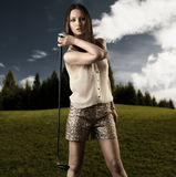 Beautiful woman with golfclub in the right hand Royalty Free Stock Photography