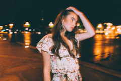 Beautiful woman in gorgeous dress. Against the backdrop of the city at night. Motion effect Royalty Free Stock Photos