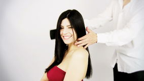 Beautiful woman with gorgeous long silky hair getting hairdo by professional hair stylist Royalty Free Stock Images