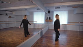 Beautiful woman gracefully dancing in front of a mirror and looking at her reflection. Cozy dance studio with a window stock footage