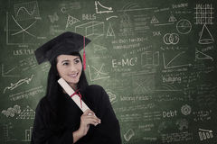 Beautiful woman graduated in class wearing graduation gown Stock Images