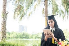 Beautiful woman graduating using tablet pc. Graduate asian woman student wearing graduation hat and gown ,background is nature in. University stock images