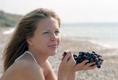 Beautiful woman with grapes on beach Stock Photo