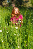 Beautiful woman among the grasses and chamomile Royalty Free Stock Photography