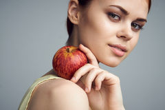 Beautiful woman on a gray background holds a strawberry at the face, portrait, berries Royalty Free Stock Photos