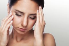 A beautiful woman on a gray background, stress and headache with. Migraine headaches, she wrestled with pain, a big portrait, high quality, professional makeup Stock Photo