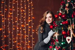 Beautiful woman in gray dress standing against decorated x-mas tree. stock images