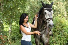 Beautiful woman and gray horse portrait in garden Stock Photography