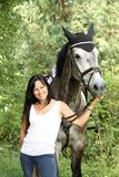Beautiful woman and gray horse portrait in garden Royalty Free Stock Photo