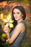 Beautiful woman in gray posing in autumnal park. Young brunette woman holding a leaf and spending time in autumn Stock Photos