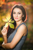 Beautiful woman in gray posing in autumnal park. Young brunette woman holding a leaf and spending time in autumn Royalty Free Stock Photos