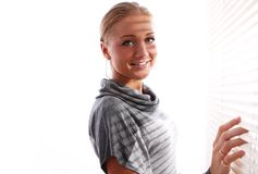 Beautiful woman in gray pullover beside a window Royalty Free Stock Photography
