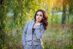 Beautiful woman in a gray suit walking in the spring park Stock Images
