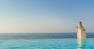 Beautiful woman in greek style on infinity pool Royalty Free Stock Photo