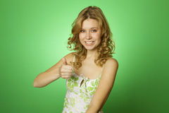 Beautiful woman on green background. Thumbs up Royalty Free Stock Images