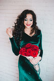 Beautiful woman in a green dress and red shoes with red roses Royalty Free Stock Photography