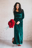 Beautiful woman in a green dress and red shoes with red roses Stock Image