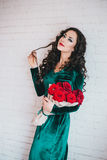Beautiful woman in a green dress and red shoes with red roses Stock Photography