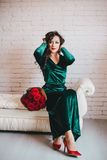 Beautiful woman in a green dress and red shoes with red roses Royalty Free Stock Images