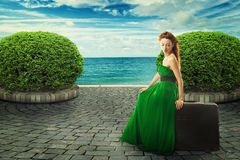 Beautiful woman in green dress sitting on a suitcase stock photo