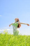 Beautiful woman in green field. Beautiful young woman in green field at blue sky background Royalty Free Stock Images