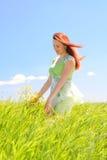 Beautiful woman in green field. Beautiful redhead young woman in green field at blue sky background Royalty Free Stock Photo