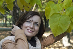 Beautiful woman with green leaves in autumn Royalty Free Stock Photo