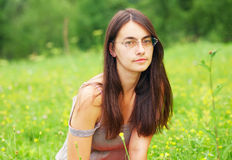 Beautiful woman on a green meadow. Portrait of a woman. She is sitting in a green meadow Royalty Free Stock Photography