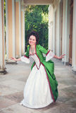 Beautiful woman in green medieval dress doing curtsey Stock Images