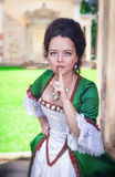 Beautiful woman in green medieval dress making silence gesture Stock Photo