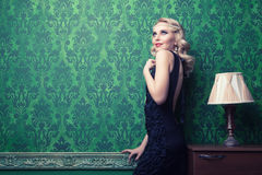 Beautiful woman in green vintage interior toned image Stock Photo