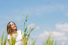 Beautiful woman with green wheat on sky background Stock Images