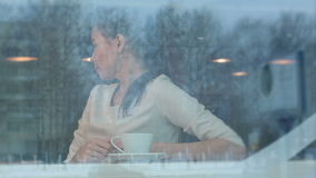 Beautiful woman greeting her male companion at a cafe. Viewed through the window. Professional shot on BMCC RAW with high dynamic range. You can use it e.g. in stock footage