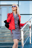 Beautiful woman in grey dress and red jacket Royalty Free Stock Images
