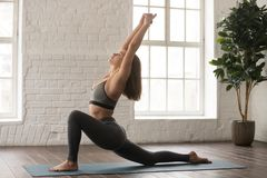 Beautiful woman practicing yoga, standing in anjaneyasana pose, Horse rider. Beautiful woman in grey sportswear, bra and leggings practicing yoga, standing in royalty free stock image