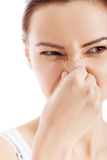 Beautiful woman with grimace beacuse of bad smell. Isolated on white stock photography