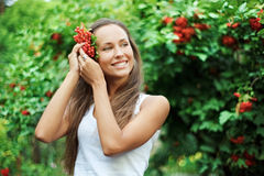 Beautiful woman with guelder rose in hair. In the garden Royalty Free Stock Photography