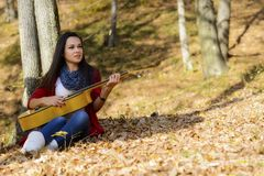 Beautiful woman guitar player girl in the forest Royalty Free Stock Image