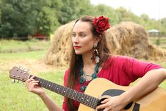 Woman with a guitar and a red rose in her hair royalty free stock images