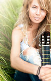 Beautiful woman with guitar sitting on grass. Stock Photo