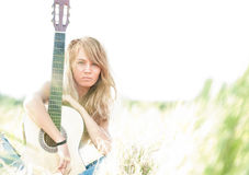 Beautiful woman with guitar sitting on grass. Royalty Free Stock Image