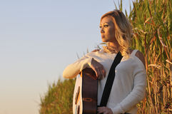 Beautiful Woman with Guitar at Sunset Stock Image