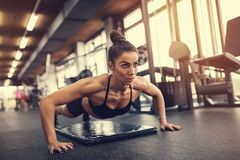 Woman doing pushups in gym stock images